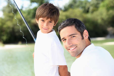 resting rod fishing: Father and son fishing together Stock Photo