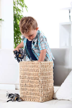 tidying up: Little boy tidying up his toys in a basket Stock Photo