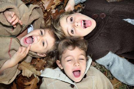 three leaf: children lying on the ground Stock Photo