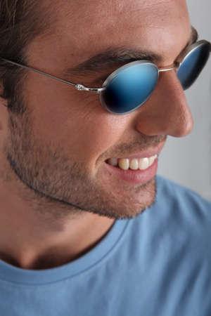 no teeth smile: Man wearing sunglasses, Stock Photo
