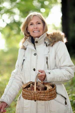 a mature woman holding a mushroom basket photo