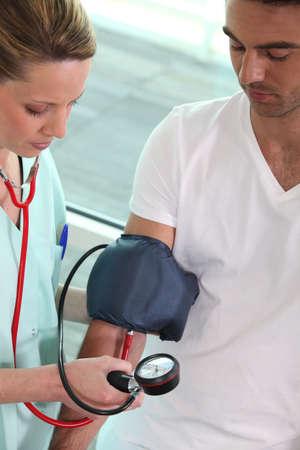 enfermera con paciente: medición de la presión arterial de un paciente de enfermera Foto de archivo