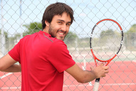 municipal court: Smiling man holding racquet by fence of municipal tennis court