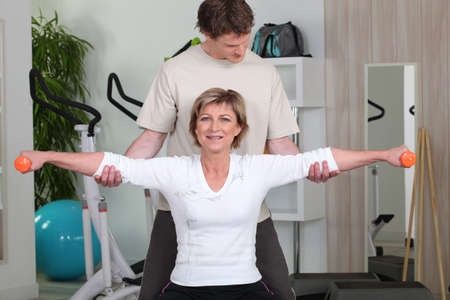 Personal trainer helping his client with her posture Stock Photo - 11088163