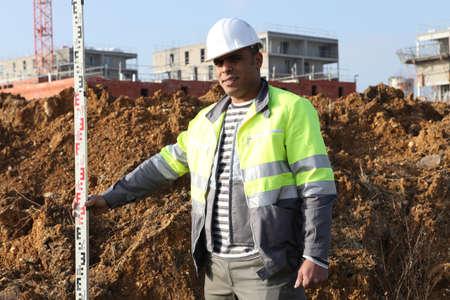 yardstick: Worker holding a yardstick