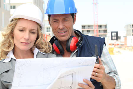 indecisiveness: Construction worker looking at an engineer Stock Photo