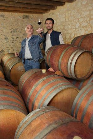 Two men tasting wine in cellar photo