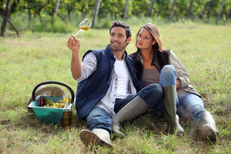 work boots: Couple drinking wine in a vineyard Stock Photo