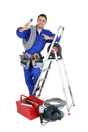 electrician tools: Male electrician surrounded by equipment