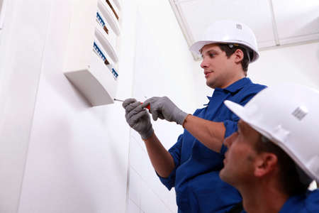 savvy: Electricians fitting a fuse box Stock Photo