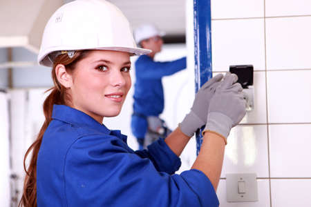 electrician tools: Young female electrician wiring a building