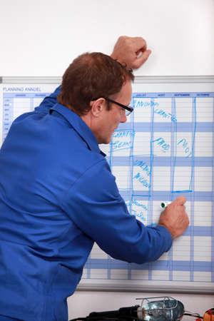 schedules: Trabajador manual escrito en un planificador de la pared Foto de archivo
