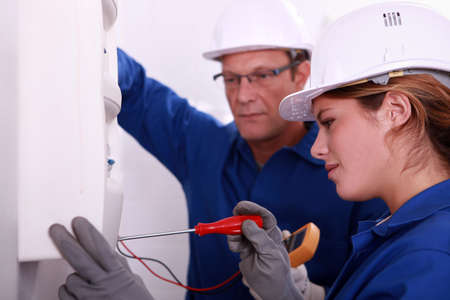 jumpsuite: a young woman working on an electricity meter accompanied with a 45 years old man, both are wearing blue jumpsuites