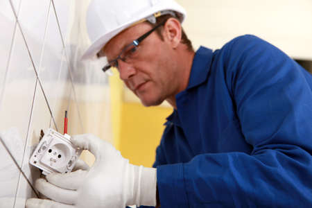 practiced: Electrical engineer fixing socket Stock Photo