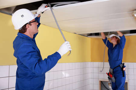 Two electricians repairing ceiling wiring photo
