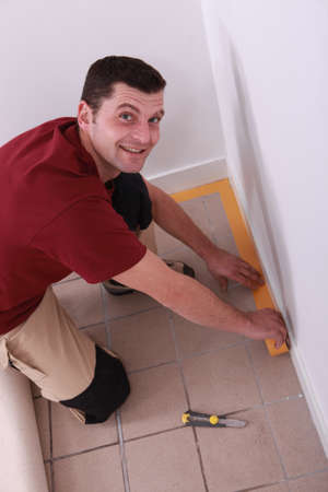 Man putting down tape around the edge of a tiled floor Stock Photo - 11116076