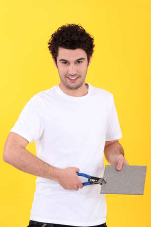 Man holding a tile and cutting it with a tool photo