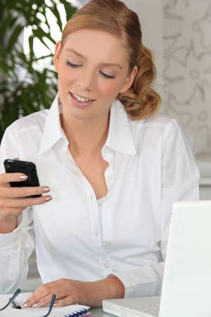 Young woman checking her cellphone at her desk photo