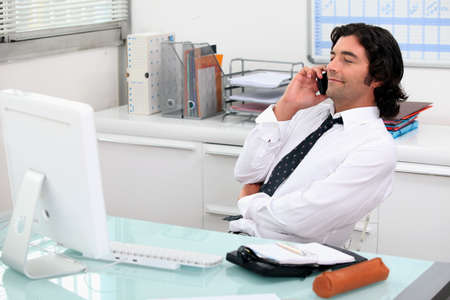Businessman using a phone at his desk photo