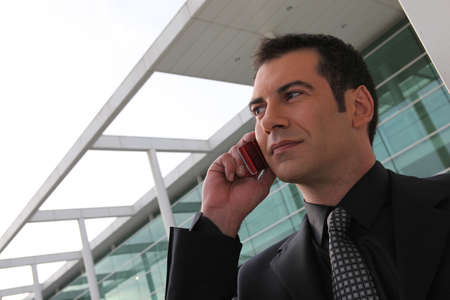 officetower: Businessman stood outside office telephoning Stock Photo