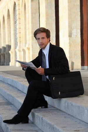 oficina antigua: elegante joven que trabaja sentado en las escaleras Foto de archivo