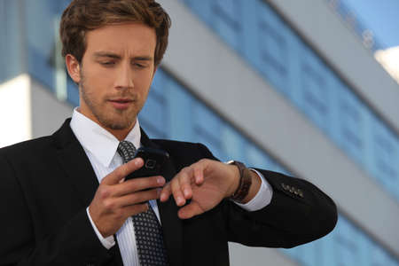 City businessman checking his watch and his phone photo