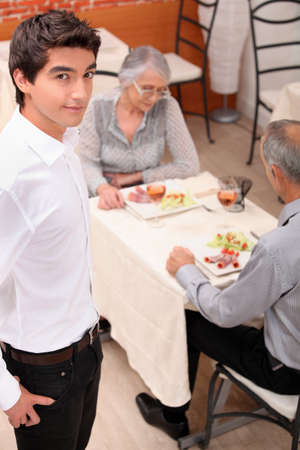 an old couple eating at restaurant and a young waiter photo