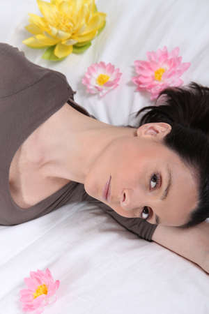 Young woman laid on a bed with flowers photo