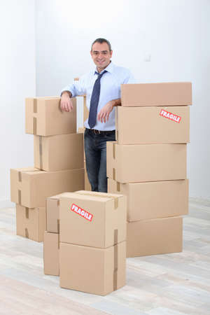obscured: Man with piles of cardboard boxes marked fragile