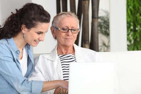 Younger and older woman sitting at a laptop photo