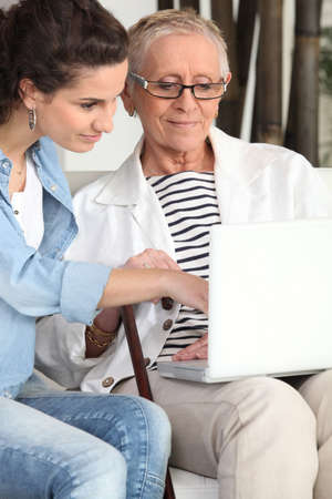 Young woman helping an elderly lady navigate the internet photo