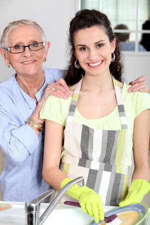 household objects equipment: Young woman doing the wash up with her grandmother Stock Photo