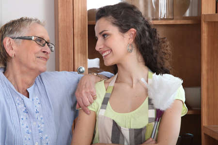 caregiver: Young woman doing the dusting for an elderly lady Stock Photo