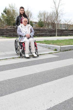 paso de peatones: Mujer que esperaba en un paso de cebra con una anciana en silla de ruedas Foto de archivo