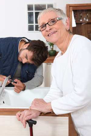 citizens: Handyman fixing a kitchen tap for a senior woman Stock Photo