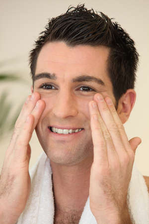 male grooming: Portrait of a smiling man applying cream