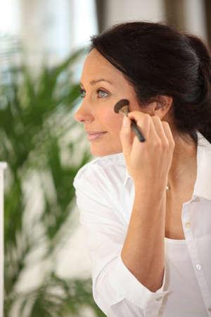 Woman applying blusher photo