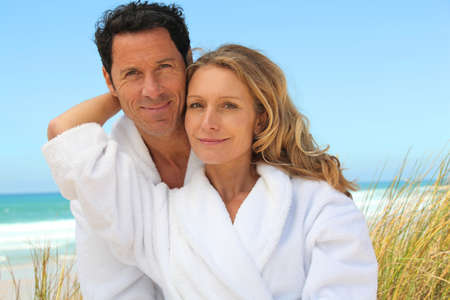 white robe: Couple relaxing on the beach in toweling robes Stock Photo
