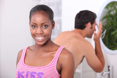black woman and his boyfriend in the bathroom, the man has a wash photo