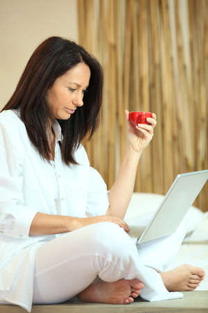 Woman using her laptop at home photo