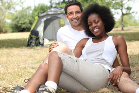 Couple camping in a grassy field photo