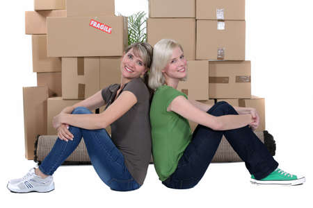 Smiling women sitting in front of stacks of cartons photo