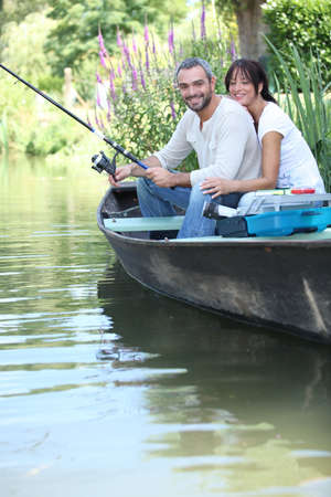 small boat: Couple fishing in a boat on a river Stock Photo