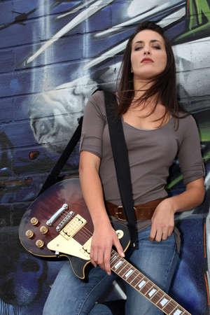 Cool female guitarist standing against graffiti photo