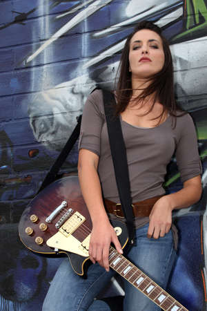Cool female guitarist standing against graffiti photo