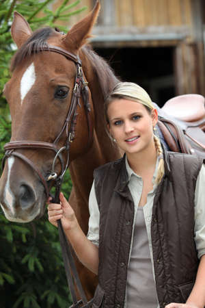 young blonde woman and a horse in front of a stable photo