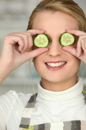 blonde wearing apron hiding eyes with cucumber slices photo