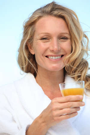 A woman wearing a dressing gown and drinking orange juice.