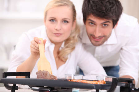 a couple facing the camera and showing meat cooked on an electric plancha cooker photo