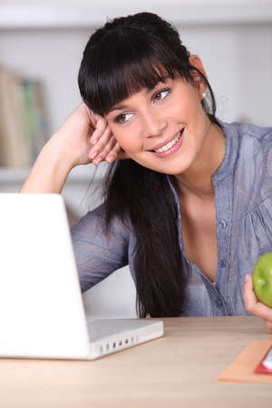 Woman working on her laptop and holding an apple photo